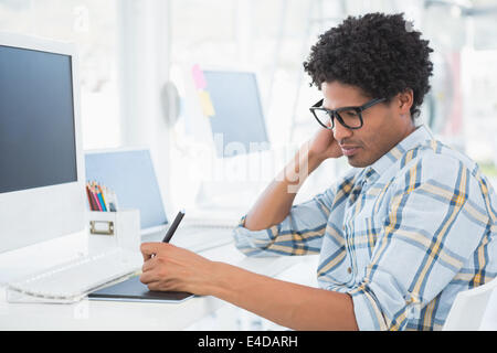 Young casual designer working with digitizer - Stock Photo