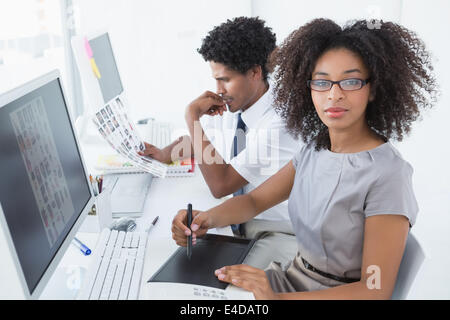 Young pretty designer looking at camera at her desk - Stock Photo