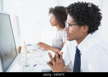 Young designer looking at computer at his desk - Stock Photo