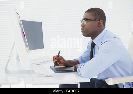 Focused businessman sitting at his desk working - Stock Photo