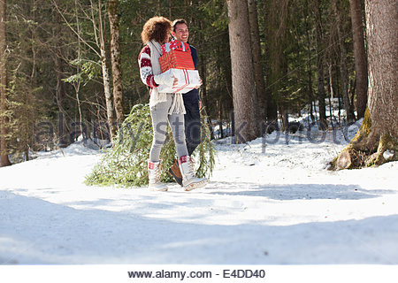 Man and woman with gifts and Christmas tree, outdoors - Stock Photo
