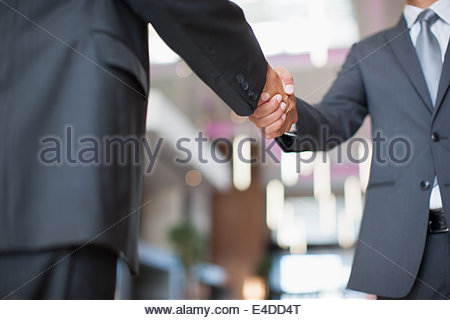 Businessmen shaking hands in office - Stock Photo