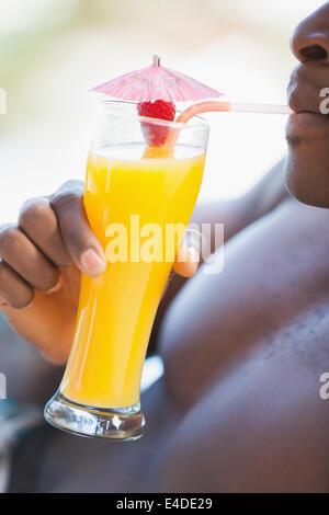 Shirtless man drinking orange cocktail - Stock Photo