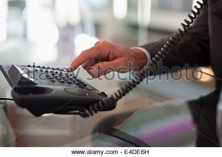 Businessman dialing telephone in office - Stock Photo