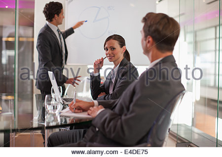 Businessman talking to co-workers in conference room - Stock Photo