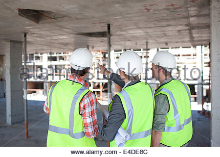 Construction workers talking on construction site - Stock Photo