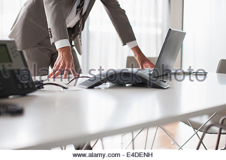 Businessman using laptop in conference room - Stock Photo