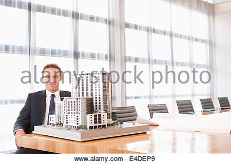 Businessman  in conference room with model building - Stock Photo