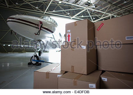 Airplane and boxes in hangar - Stock Photo