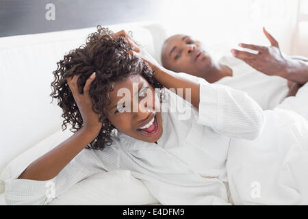 Young couple arguing in bed - Stock Photo