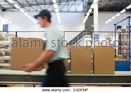 Worker carrying box in shipping area - Stock Photo