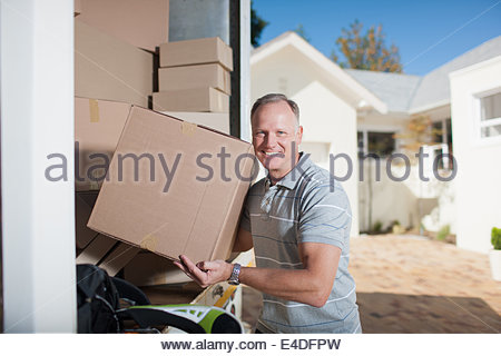 Smiling man carrying box from moving van - Stock Photo