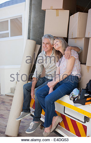Couple sitting in back of moving van - Stock Photo