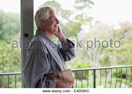 Senior man talking on cell phone on balcony - Stock Photo