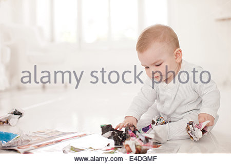 Baby on floor with crumpled paper - Stock Photo