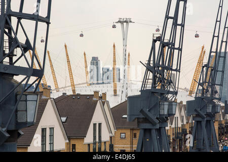 The O2 Arena and the Emirates air line cable car behind apartments on the Royal Victoria Dock, with old cranes. - Stock Photo