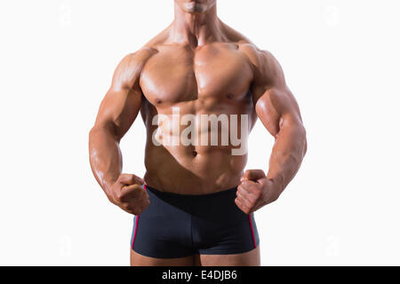 Mid section of a muscular young man clenching fists - Stock Photo