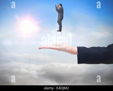 Composite image of businessman standing on ladder - Stock Photo