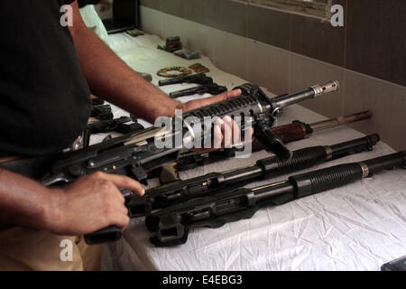 Lahore, Pakistan. 9th July, 2014. A policeman displays seized weapons to media in eastern Pakistan's Lahore on July - Stock Photo