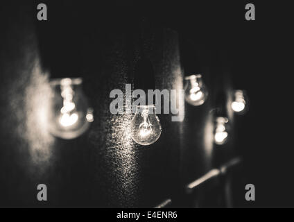 Black and white photograph of five lightbulbs against a black textured background. - Stock Photo