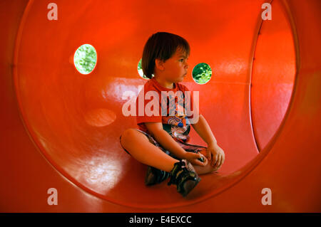 Toddler Sitting In Tunnel on Playground at the Louisville Zoo in Kentucky - Stock Photo
