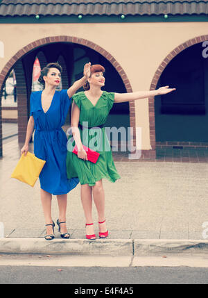 Two beautiful girls in retro style  hailing  taxi in the street - Stock Photo