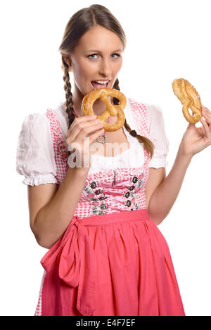 Happy attractive german or bavarian woman in a traditional dirndl opening her mouth to eat a fresh pretzel - Stock Photo