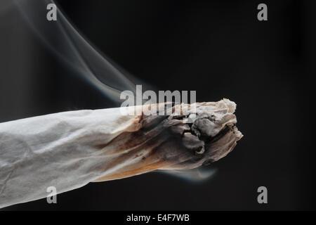Burning marijuana joint - Stock Photo