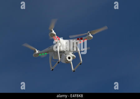 small unmanned helicopter with a camera floating in the blue sky - Stock Photo
