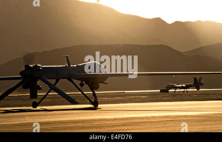 An MQ-1 Predator and MQ-9 Reaper unmanned aerial vehicle taxi to the runway in preparation for take-off at sunset - Stock Photo