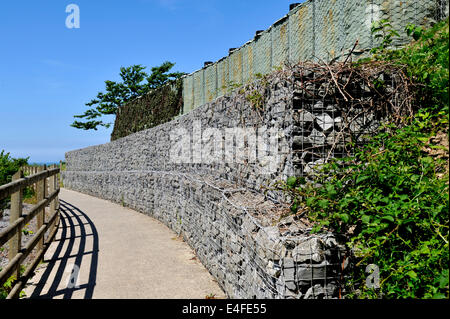Embankment retaining wall constructed with gabion wire mesh baskets filled with rock with bastion boxes at top, - Stock Photo