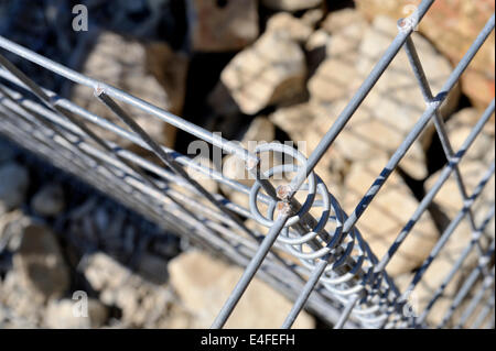 Close-up detail of galvanized wire mesh basket babion filled with rock for slope stabilization,  Aberporth, Wales, - Stock Photo
