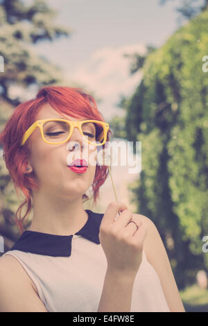Beautiful hipster teenage girl blowing a dandelion, looking happy, closeup - Stock Photo