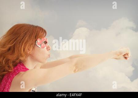 Superhero girl pretending to be flying - Stock Photo