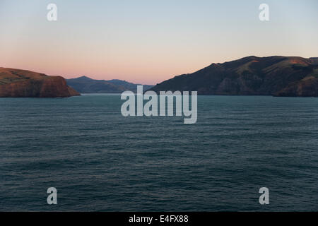 First sunlight illuminating the hills around Akaroa - Stock Photo