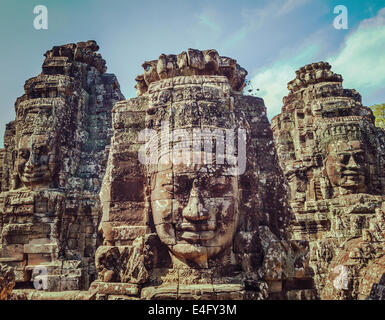 Vintage retro effect filtered hipster style travel image of ancient stone faces of Bayon temple, Angkor, Cambodia - Stock Photo