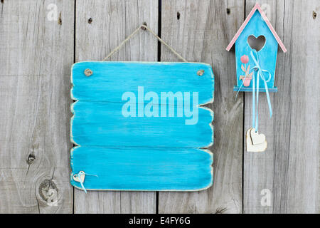 Blank teal blue sign hanging on fence next to blue and pink birdhouse with hearts hanging by ribbon - Stock Photo