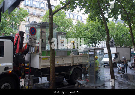 Workers removing public telephone kiosks in Paris, Blvd St Germain - Stock Photo