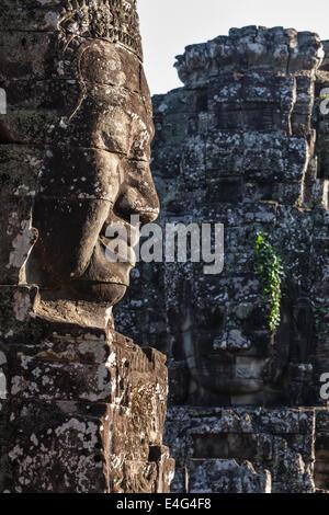 Ancient stone faces of Bayon temple, Angkor, Cambodia - Stock Photo