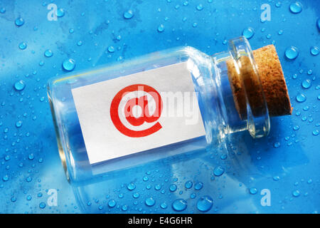 E-mail @ symbol message in a bottle - Stock Photo