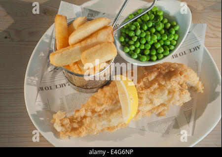 Fish and chips (Deep fried Haddock in batter) with peas and a segment of lemon  on a white plate on a wooden table - Stock Photo