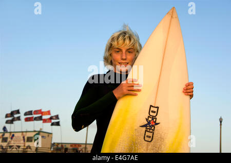 Young surfer  at Huntington Beach Pier - Stock Photo