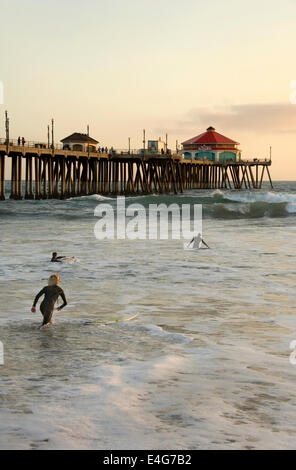 Surfers at Huntington Beach Pier - Stock Photo
