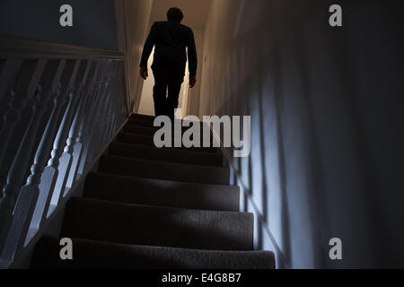 Silhouette of a man walking upstairs back view, shadows cast on the walls from the light below. - Stock Photo