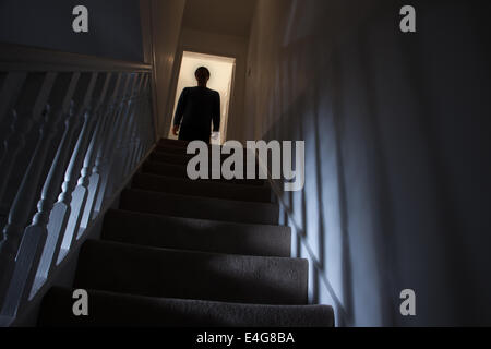 Silhouette of a man standing at the top of a stairway, shadows cast on the walls from the light below. - Stock Photo