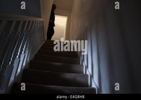 Silhouette of a man leaning against the wall at the top of a stairway, shadows cast on the walls from the light - Stock Photo