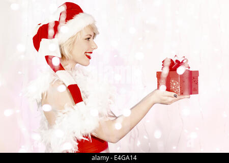 Young woman in Santa Claus costume holding gift box - Stock Photo