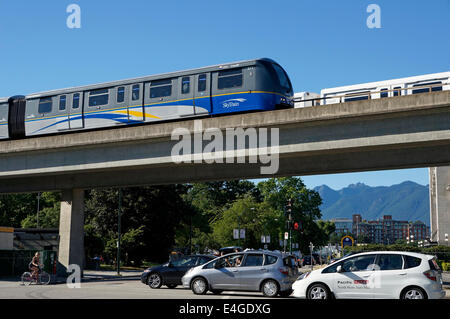 The Skytrain elevated light rapid transit system crossing over a busy street with cars and a bicycle, Vancouver, - Stock Photo