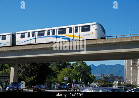 The Skytrain elevated light rapid transit system crossing over a busy street, Vancouver, BC, Canada - Stock Photo