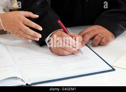 Bride and Groom Signing Marriage Certificate in the church - Stock Photo